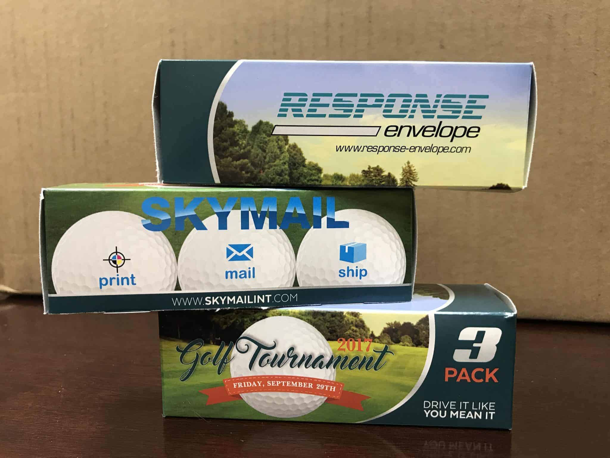 Three of Skymail International's three-ball custom golf ball cases stacked on top of each other.